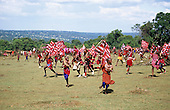 Lolgorian, Kenya. Siria Maasai; Eunoto ceremony; moran carrying flags running through the Manyatta.