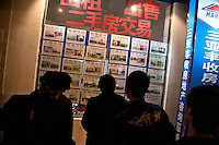 People look at real estate listings in Sanya, Hainan, China.