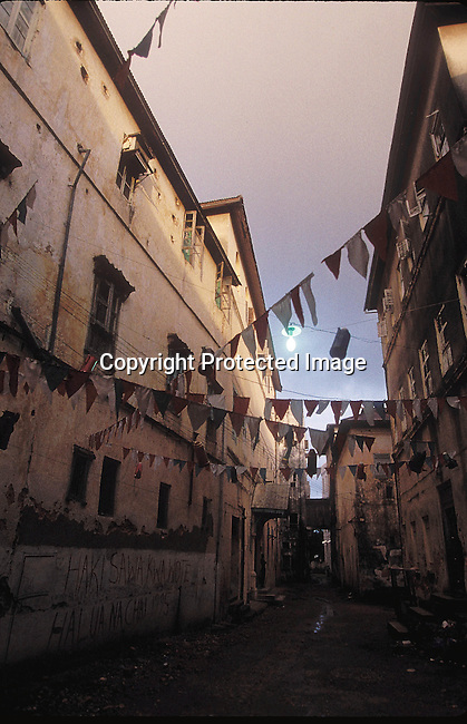 COTANZA35037.Country. Tanzania. Zanzibar. Street between buildings with cloth banners hanging between the buildings. 8/95. Narrow ally..©Per-Anders Pettersson/iAfrika Photos
