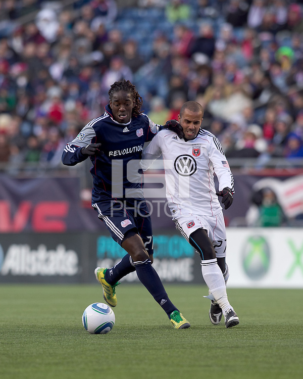 New England Revolution midfielder Shalrie Joseph (21) brings the ball forward as DC United forward Fred Carreiro (27) defends. In a Major League Soccer (MLS) match, the New England Revolution defeated DC United, 2-1, at Gillette Stadium on March 26, 2011.