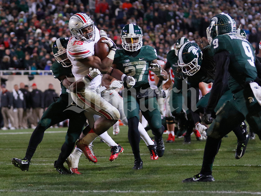 Ohio State Buckeyes running back Ezekiel Elliott (15) fights through Michigan State defenders to score a touchdown during the fourth quarter of the NCAA football game at Spartan Stadium in East Lansing, Michigan on Nov. 8, 2014. (Adam Cairns / The Columbus Dispatch)