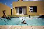 Oscar Dube, a young successful black man takes dip in the pool with his daughter's cousins on March 25, 2002 in Johannesburg, South Africa. Oscar works for the Swedish mobile phone and equipment maker. A growing number of people belong to the new black elite in the country. Well educated and connected, they have risen from the poverty in the townships to a very different lifestyle, since the fall of Apartheid and the start of democracy in the country in 1994. (Photo by: Per-Anders Pettersson)