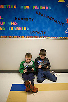 Children play video games in a hallway outside a Romney town hall campaign event at McKelvie Intermediate School in Bedford, New Hampshire, on Jan. 9, 2012.  Romney is seeking the 2012 Republican presidential nomination.