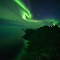 Northern lights shine in sky over mountains of Moskenesøy, Lofoten Islands, Norway