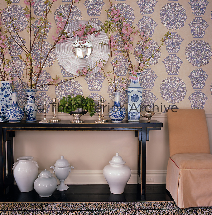 The oriental theme of the wallpaper in the dining room is echoed in the arrangement of blue and white porcelain vases filled with cherry blossom