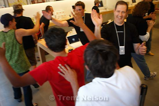 Salt Lake City - Apple employees welcome in the first customers. Tommy Oyarzun waited in line for twenty-six hours to get the first Apple iPhone sold at the Gateway Apple Store Friday afternoon.  .; 6.29.2007