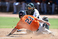 Oakland Athletics catcher Iolana Akau (33) attempting to tag Trevor Brown (21) sliding into home during an instructional league game against the San Francisco Giants on September 27, 2013 at Papago Park Baseball Complex in Phoenix, Arizona.  (Mike Janes/Four Seam Images)