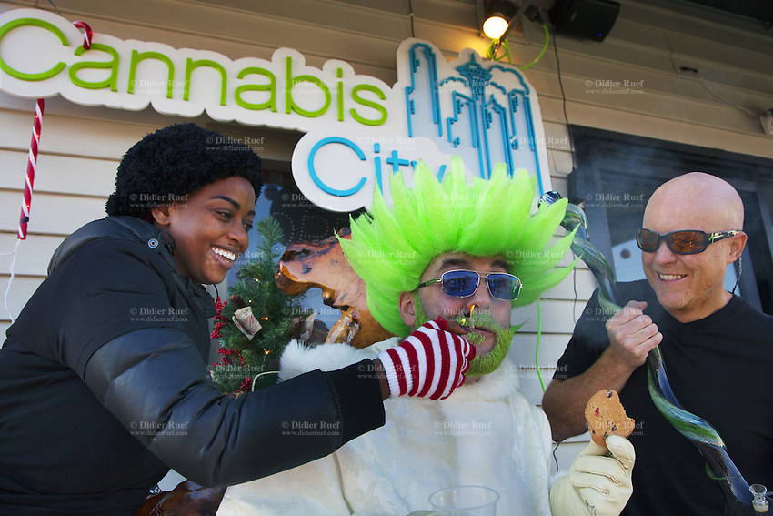 USA. Washington state. Seattle. Canna Santa at Cannabis City. Canna Santa is the jolly green counterpart to the traditional Santa Claus with red coat, also known as Saint Nicholas, Father Christmas or Santa. Canna Santa smokes a joint and holds a chocolate cookie in his left hand. Cannabis City is authorized, according to cannabis legalization in Washington State, to sell marijuana as a retail store front. Cannabis City was the first state-licensed store for recreational marijuana open in July 2014. Cannabis, commonly known as marijuana, is a preparation of the Cannabis plant intended for use as a psychoactive drug and as medicine. Pharmacologically, the principal psychoactive constituent of cannabis is tetrahydrocannabinol (THC); it is one of 483 known compounds in the plant, including at least 84 other cannabinoids, such as cannabidiol (CBD), cannabinol (CBN), tetrahydrocannabivarin (THCV), and cannabigerol (CBG). 14.12.2014 © 2014 Didier Ruef