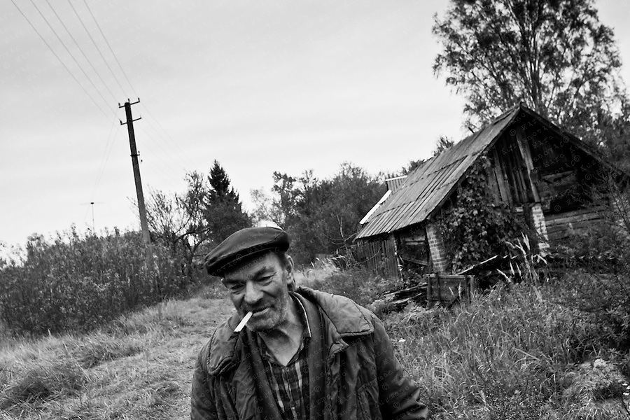 An elderly man walks true his abandoned village. He never left the exclusion zone near Prypiat.