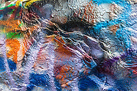 Layers of paint peel away from the surface of their host at Cadillac Ranch in Texas.
