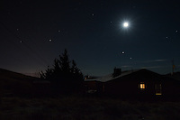 Moonlight over a house in the hills around Prescott, Arizona.  The moonlight reflects off of the roof, framing the otherwise-backlit house.  The lights of Prescott Valley, AZ can be seen behind a juniper, and a few stars can be seen despite the moon's illumination.
