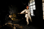 Rajkumar, a factory worker, shovels coal into a drier during the drying process at the Makaibari Tea estate, in Darjeeling, India.