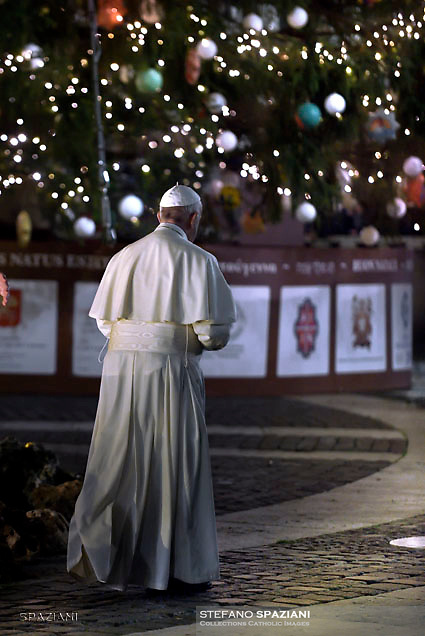 Pope Francis prays in front of a Nativity scene in St Peter's square at the Vatican  on December 31, 2017