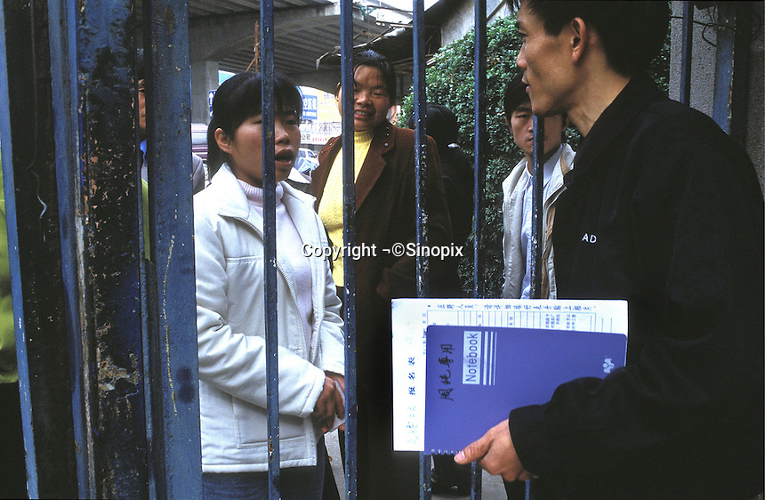 A jobseeker talks to a factory manager at a factory gate in Guangzhou, China..14 Feb 2001.