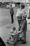 American family group together in street  Pendleton, Oregon 1969. Smoking a pipe, mother with hair in rollers.