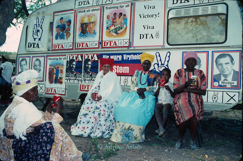 Herero women in traditional dress sit in the shade of a DTA caravan during the 1989 independence  elections, Grootfontein,Namibia. with free cans of coke given out by the DTA which was a largely a  white run party with links to the South African regime. .
