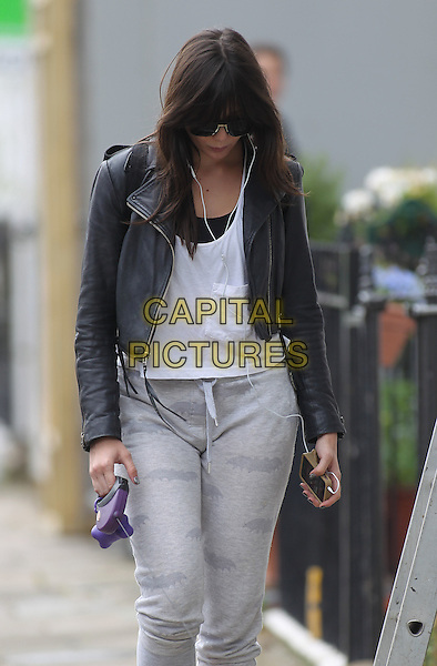Daisy Lowe in Primrose Hill, London, England..August 1st, 2012.half 3/4 length jeans denim grey grey joggers  white top jacket leather sunglasses shades looking down ipod iphone headphones .CAP/HIL.©John Hillcoat/Capital Pictures.