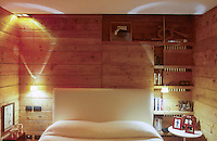 The walls of the bedroom are clad in wooden planking which incorporates a set of open shelves that partially conceal a floor to ceiling radiator