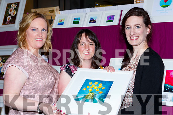 Killarney artist Amelie Gagne right shows Karen Nagle Castlemaine and Lorraine McDonnell Barradubh one of her paintings  at the Killarney Rotary club Wine+Art night in the Malton Hotel on Saturday night