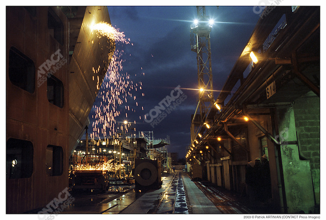 Construction of Queen Mary 2, Alstom Marine, Chantiers de l'Atlantique, Saint-Nazaire, France, December 2002. Blowlamp cutting.