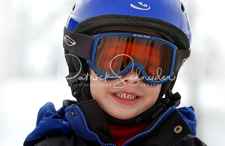 A young boy wearing goggles while skiing at Sugar Mountain Ski Resort in NC.