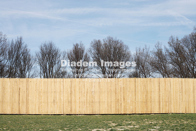 A wooden fence separating a rough grassy area from some trees.