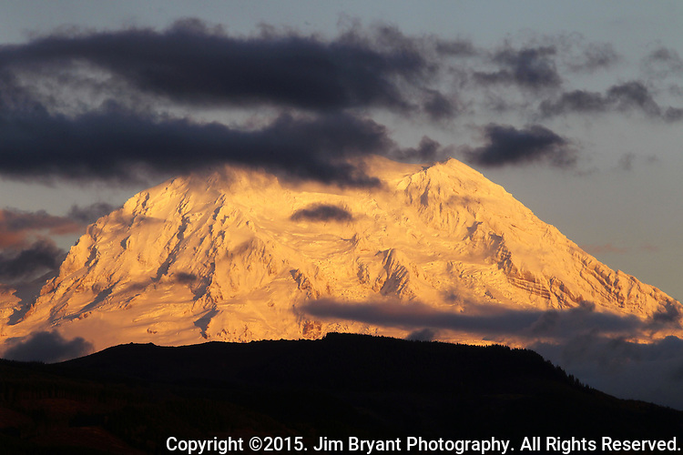 Mt. Rainier surrounded by clouds. The 14,411 foot volcano which covers 228,480 acres was designated a National Park in 1899. Washington.  Jim Bryant Photo. ©2015. All Rights Reserved.