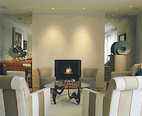 The focal point of this elegant living room is the contemporary fireplace with its decorative plaster surround designed in swirling abstract shapes
