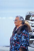 89 year old native Alaska woman, Bertha Leavitt in traditional Parka, leans against an Umiak (whaling boat) on the beach of Arctic Ocean, Utqiagvik (Barrow), Alaska. (taken in 2000)