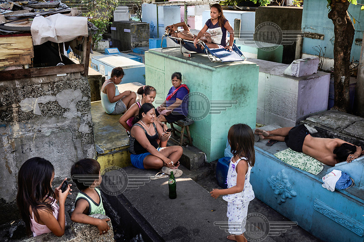Residents socialise on tombs in Manila North Cemetery.  Manila North Cemetery is home to thousands of 'informal settlers' who have built shacks using in and around the mausoleums, crypts and tombs. In comparison to the city's dangerous shantytowns the cemetery is relatively quiet and safe. However, water must be collected from a few public wells and the electricity supply is erratic, usually stolen from mains cables. In the summer the sweltering heat drives people to sleep outside often on top of the tombs.<br /> <br /> Some of the residents live in the crypts and mausoleums of wealthy families, who pay them a stipend to clean and watch over them. Others make a living carving headstones or selling candles to visitors and helping out at funerals as the daily life of the cemetery goes on around the people who live there.