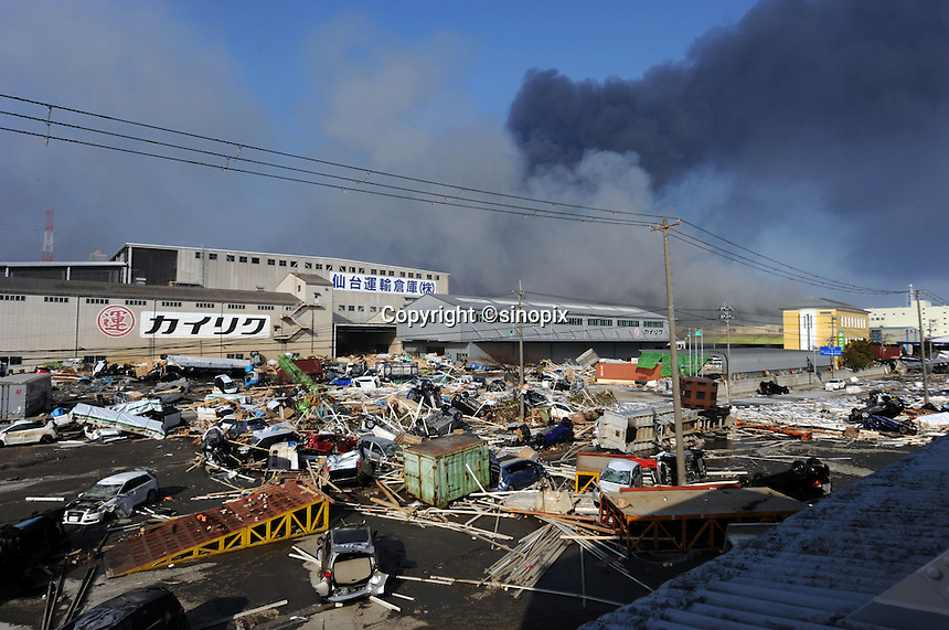 Plumes of smoke rise behind Sendai port and the devastated factories, Sendai, Japan. One of the biggest earthquakes ever recorded struck off the coast of Japan on 11 Mar 2011 had killed thousands of people. The death toll was expected to rise dramatically, with tens of thousands reported missing.<br /> 13 Mar 2011
