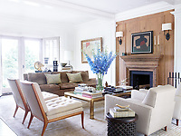 In the living room, the panelled walls are decorated in off-white and neutral tones, the midcentury furnishings include a Florence Knoll sofa covered in a Quadrille velvet, Harvey Probber armchairs in a Brunschwig & Fils fabric, and T.H. Robsjohn-Gibbings slipper chairs; the 1960s cocktail table is by Mastercraft, the mantel is original to the house, the artwork to the left of it is by Jean-Marc Louis, the sconces are by Thomas O'Brien for Visual Comfort, and the rug is from ABC Carpet & Home.
