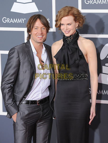 KEITH URBAN & NICOLE KIDMAN.Arrivals at the 52nd Annual GRAMMY Awards held at The Staples Center in Los Angeles, California, USA..January 31st, 2010.grammys half length married husband wife grey gray silver suit black dress sleeveless halterneck white shirt tall short hand in pockets beads beaded  .CAP/RKE/DVS.©DVS/RockinExposures/Capital Pictures