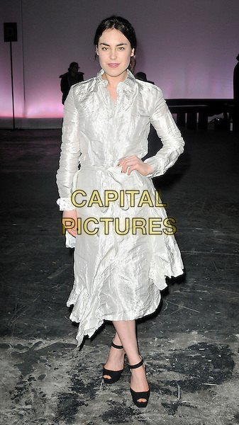 Tallulah Harlech.The J.W Anderson show during the London Collections at the Old Sorting Office, New Oxford Street, London, England..9th January 2013  .full length silver jacket coat mac hand on hip white black ankle strap peep toe shoes .CAP/WIZ.© Wizard/Capital Pictures.