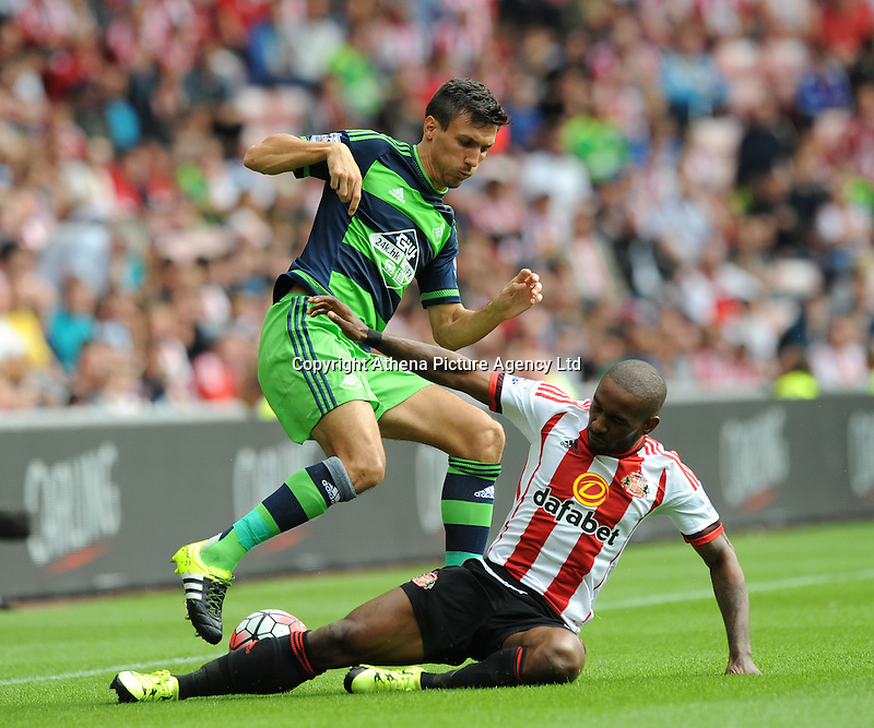 Jermain Defoe of Sunderland flies in with a challenge on Jack Cork of Swansea City during the Barclays Premier League match between Sunderland and Swansea City played at Stadium of Light, Sunderland