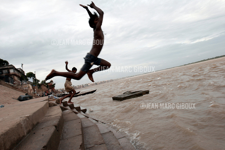 """.VARANASSI, UTTAR PRADESH, INDIA - SEPTEMBER 13, 2005 : Kids dive from the ghats into the monsoon swollen Gange river in the holi city of Varanassi. Varanassi, also named Benares or Kachi, is one of the holiest place for Hindus in India, drawing millions of pilgrims every year. They come to prey to along the temples lining the ghats, and purify themselves in the """"Holi Ganga"""".(Photo by Jean-Marc Giboux)"""