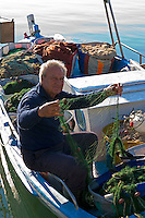 CYPRUS, Agia Napa (Ayia Napa): Limanaki, small harbour of popular holiday resort - fisherman mending flew<br />
