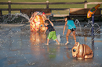 Three young children enjoy the chaos of the splash pad at Stanton Central Park.