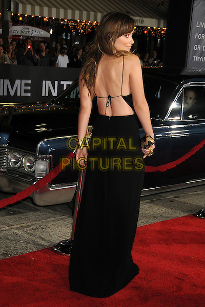 Olivia Wilde.The Regency Enterprises L.A. Premiere of 'In Time' held at The Regency Village Theatre in Westwood, California, USA..October 20th, 2011.full length gold clutch bag black sleeveless dress backless straps looking over shoulder .CAP/ADM/BP.©Byron Purvis/AdMedia/Capital Pictures.