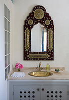 A Moroccan style mirror with metal panels hangs above a marble topped, built-in wash stand
