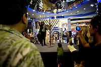 Chanuka candles are lit on the stage as Rabbi Kantor (Chabad Bangkok, Sukhimvit Soi 22) leads in song and prayers, during the Chanuka celebrations organised by Chabad Bangkok on 13th December 2009, at Paragon Mall's IMAX theater, Bangkok, Thailand..Photo by Suzanne Lee / For Chabad Lubavitch