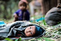 Little Halima rests on the forest floor, while her parents pack the saddlebags.