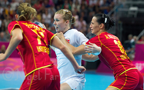 11 AUG 2012 - LONDON, GBR - Karoline Dyhre Breivang (NOR) (centre) of Norway looks for a way past Majda Mehmedovic (MNE) (left) and Andjela Bulatovic (MNE) (right) of Montenegro during the women's London 2012 Olympic Games handball final at the Basketball Arena in the Olympic Park, in Stratford, London, Great Britain (PHOTO (C) 2012 NIGEL FARROW)