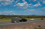 Pickup truck tows utility trailer with mountains in the background