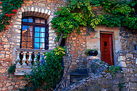 The facade of a stone house with a balcony and creeping plant archway. Comillon, France.