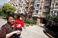 Li Fang (gauche) et sa petite-fille Li Siqi (droite) sortent de l'appartement familial de 100 m2, et parcourent la résidence, près de Shanghai, le 7 mai 2008. Depuis sa construction, l'immeuble a été rénové, des colonnes et de fausses briques ont été rajoutées, faisant de l'édifice un bâtiment typique de ces nouvelles classes moyennes chinoises. Li Fang regrette de ne pas avoir investi dans l'immobilier, car l'appartement qu'il loue a pris cinq fois sa valeur. « Il y a 20 ans, ici, ce n'étaient que des champs, nous confie Qu Hue, une voisine. Maintenant, il y a beaucoup de bébés, de chiens et de voitures ! » - trois signes d'une classe qui s'enrichit. Photo par Lucas Schifres/Pictobank