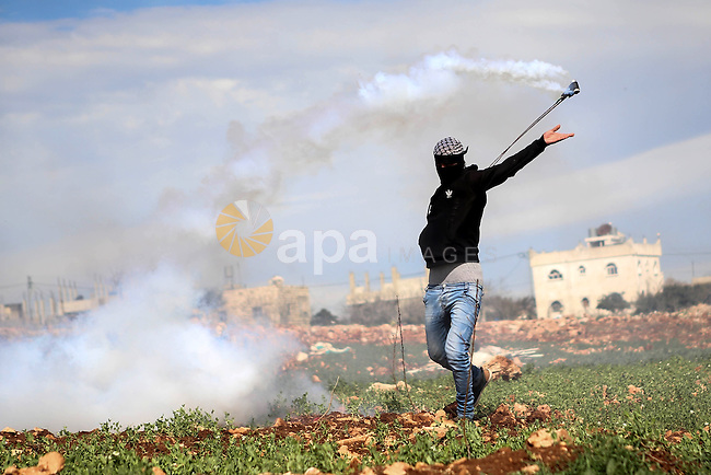 A masked Palestinian protester uses a sling shot to hurl back a tear gas canister at Israeli troops during clashes at a weekly protest against Jewish settlements, in the West Bank village of Nabi Saleh, near Ramallah February 6,2015. Photo by Shadi Hatem