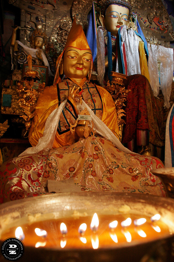 Yak butter candles and a statue of one of the Dalai Lamas surround a statue of Jampa, the future Buddha, at the Main Assembly Hall at  Sera Monastery in Lhasa, Tibet.  Photograph by Douglas ZImmerman