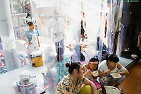 People eat noodles in the entrance of the Dazheng shopping mall at lunchtime in eastern Yuzhong District, Chongqing, China.