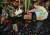 NWA Media/Michael Woods --12/20/2014-- w @NWAMICHAELW...Springdale firefighter Mike Blain helps Annabell Bell, age 8, Colt Bell, age 8 of Springdale, and their grandmother Madella Dodson with their gifts Saturday morning at Lokomotion Family Fun Center during the Springdale firefighters annual Christmas event for less fortunate children.  Springdale firefighters treated the kids with food, rides, games, and gifts from Santa.